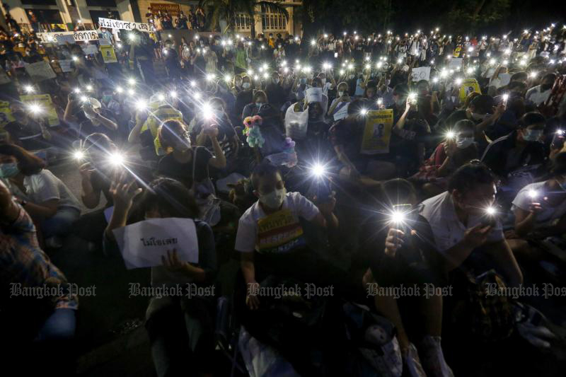 Students at Kasetsart University hold their flashing mobile phones aloft as part of their protest against the government at the main campus in Bang Khen on Friday. (Photo by Pattarapong Chartpattarasill)