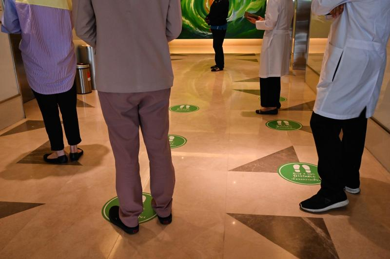 In this photo taken July 24, 2020 doctors, staff and visitors stand on social distancing markers on the floor while waiting for an elevator in a hospital in Bangkok, to observe restrictions in place to halt the Covid-19 coronavirus. (AFP)