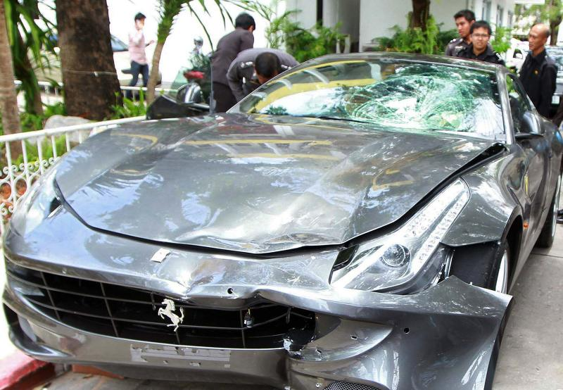 In this file photo taken on Sept 3, 2012, police officers look at a Ferrari that was allegedly involved in a hit-and-run accident during their investigation at Thong Lor police station in Bangkok. (AFP photo)
