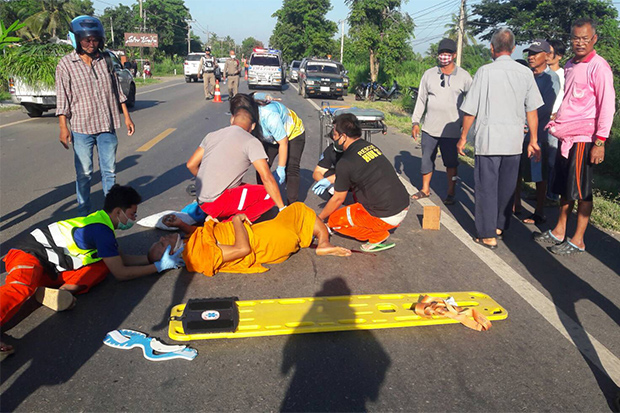 Rescue volunteers help a monk after a motorcycle with a sidecar was hit by a pick-up in Phimai district in Nakhon Ratchasima on Sunday. (Photo by Prasit Tangprasert)