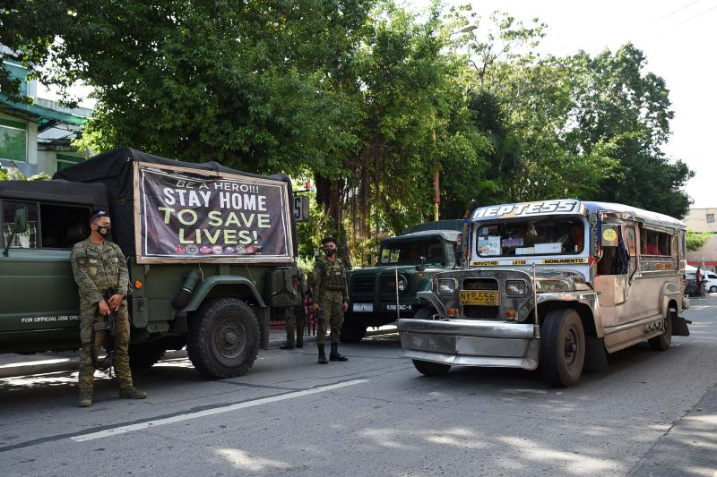 Armed soldiers stand next to their vehicles as a passenger jeepney speeds past along a street in Navotas in suburban Manila on July 16, 2020, after the local government reimposed a lockdown in the city due to increased Covid-19 infections. (AFP photo)