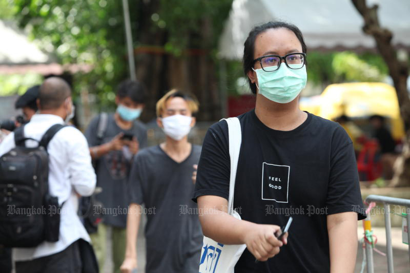 Men wear face masks as they enter Wat Sam Phraya in Phra Nakhon district on Thursday for an army conscription draw. (Photo by Apichart Jinakul)