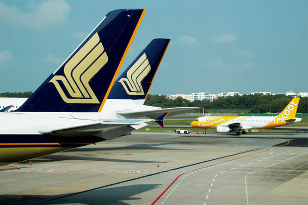 Singapore Airlines and Scoot planes are pictured on the tarmac at Changi Airport on March 11, 2020. (Reuters photo)