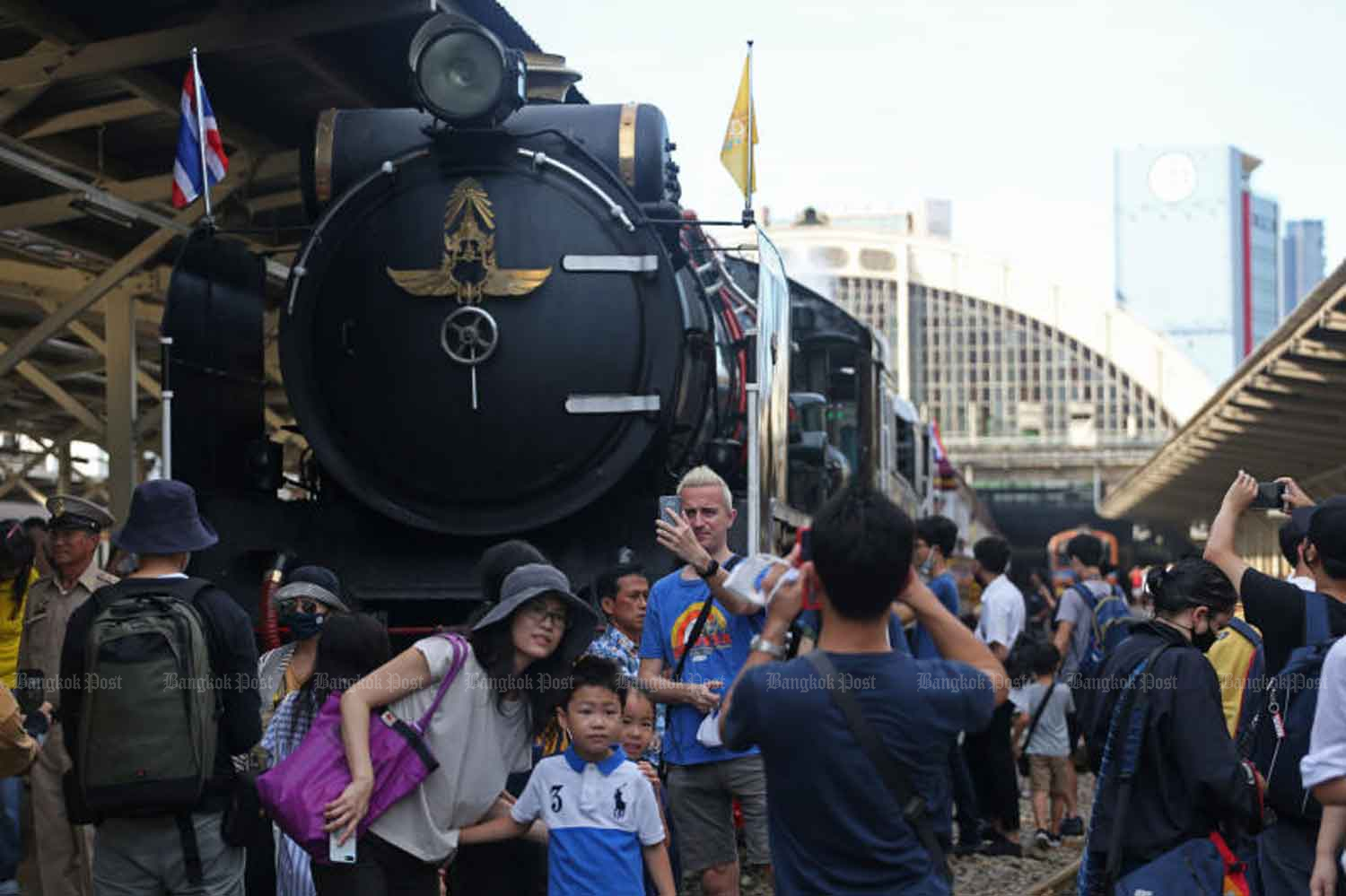 People take photos with an old steam engine the State Railway of Thailand operated from Hua Lamphong railway terminus in Bangkok to celebrate His Majesty the King's birthday on Tuesday, when the country logged two new Covid-19 cases. (Photo: Varuth Hirunyatheb)