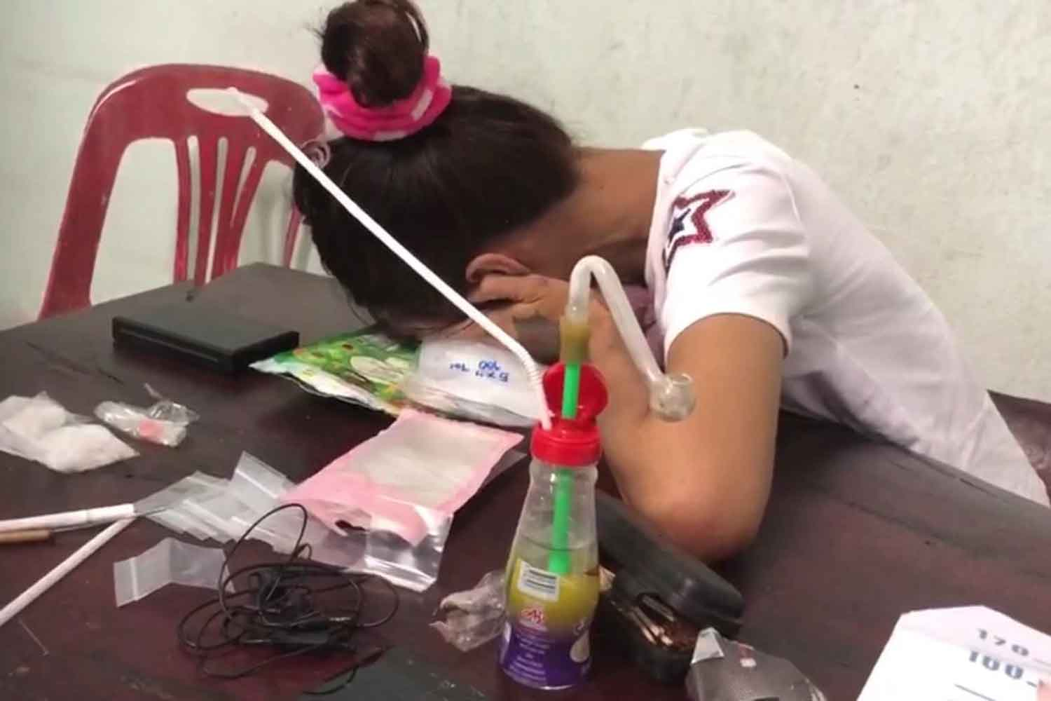 Kittima Ronnakan hides her face after police raided her house in Hat Yai, Songkhla, searching for drugs. Her husband fled as they burst in. (Photo: Assawin Pakkawan)