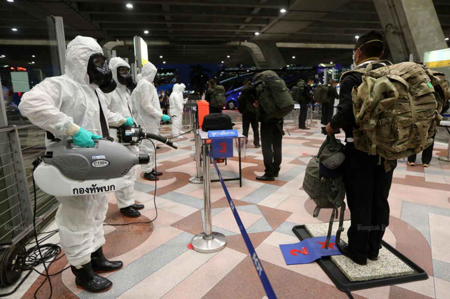 Disease control personnel disinfect soldiers who returned from an exercise in Hawaii, at Suvarnabhumi airport in Samut Prakan province on July 22. (Photo: Wichan Charoenkiatpakul)