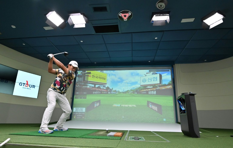 A South Korean golfer drives in a simulation booth during the GTour screen golf tournament in Daejeon, south of Seoul.