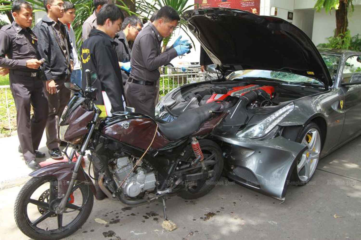 Forensic police inspect a motorcycle belonging to Pol Snr Sgt Maj Wichian Klanprasert of Thong Lor police station and a Ferrari driven by Vorayuth Yoovidhya, the youngest son of Red Bull executive Chalerm Yoovidhya, following the accident in September 2012. (Photo: Somchai Poomlard)