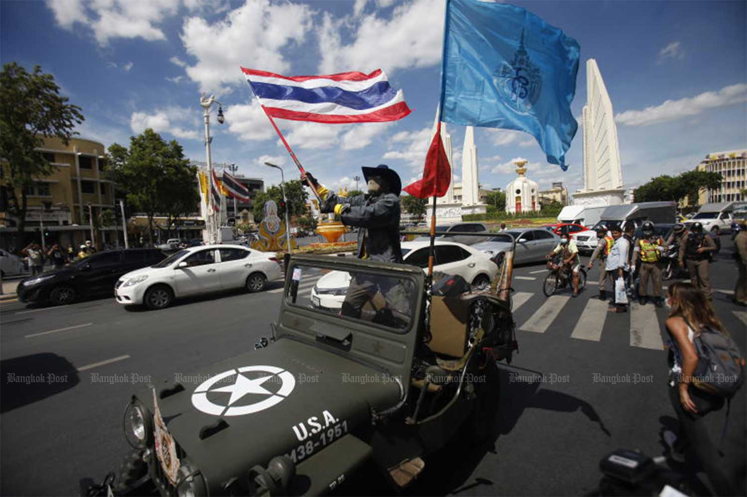 A demonstrator waves the national flag as the pro-government Archeewa Chuay Chart (Vocational Students Helping the Nation) stages a rally at the Democracy Monument on Ratchadamnoen Avenue. (Photo by Nutthawat Wicheanbut)