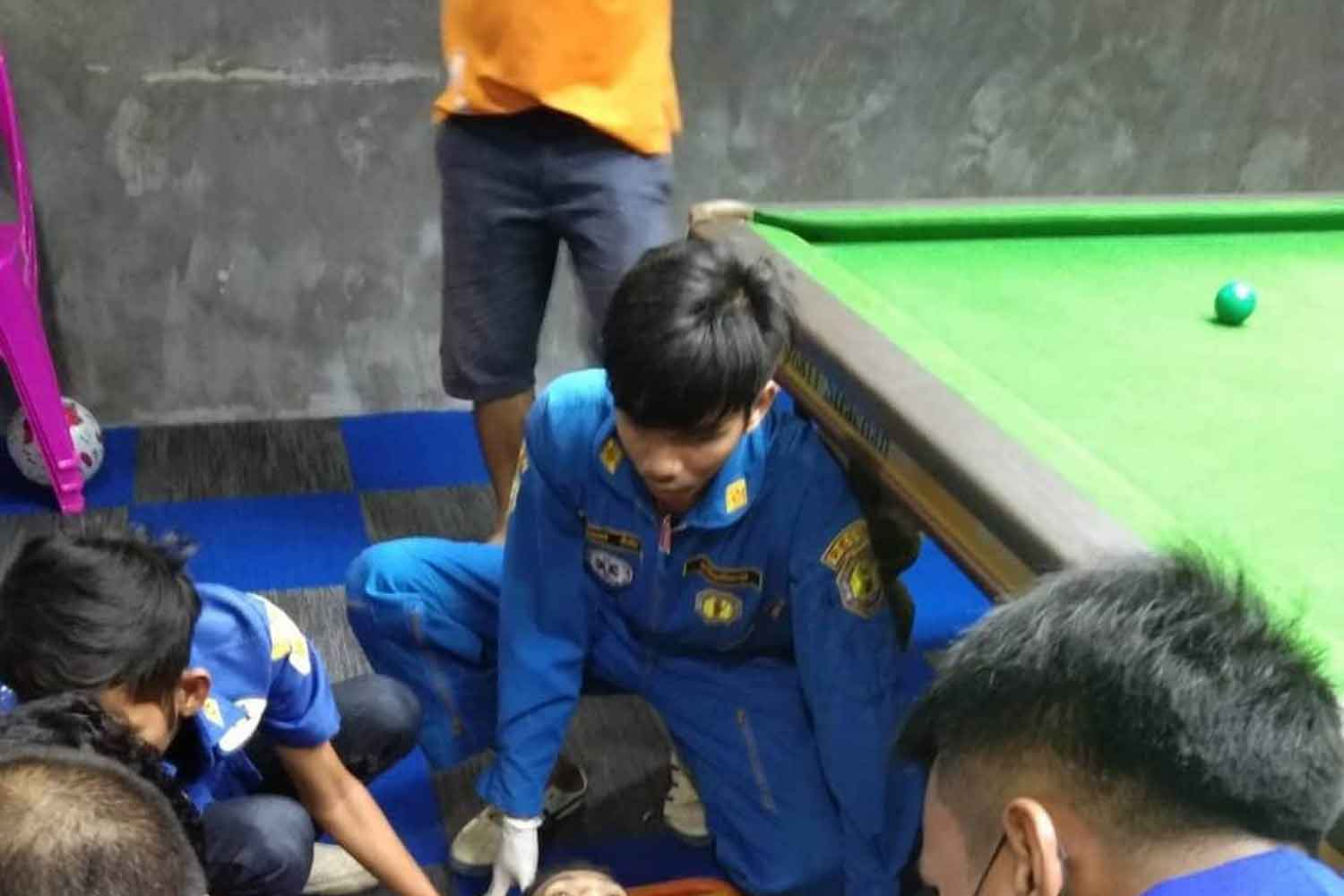 Rescue workers treat the grievously wounded victim at his snooker club before rushing him to hospital, in Tha Maka district of Kanchanaburi, on Thursday night. He died. (Photo: Piyarat Chongcharoen)