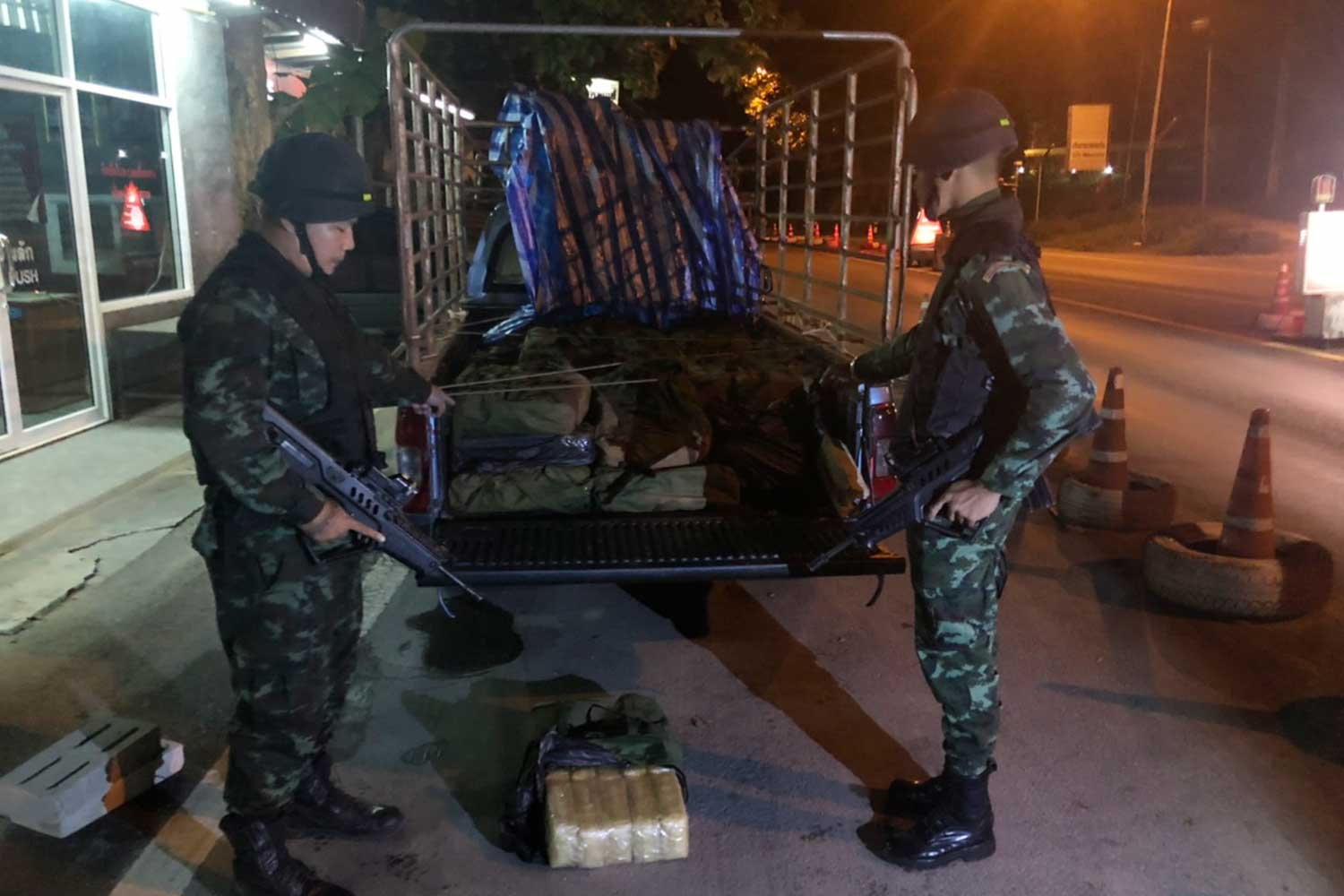 Soldiers search a pickup truck and find 4 million speed pills hidden in 40 green backpacks at a checkpoint in Chai Prakan district of Chiang Mai early Thursday. (Photo by Phanumet Tanraksa)