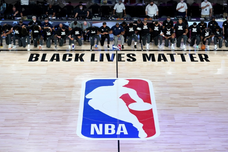 Members of the Utah Jazz and New Orleans Pelicans kneel during the US national anthem as the NBA restarts in Orlando.