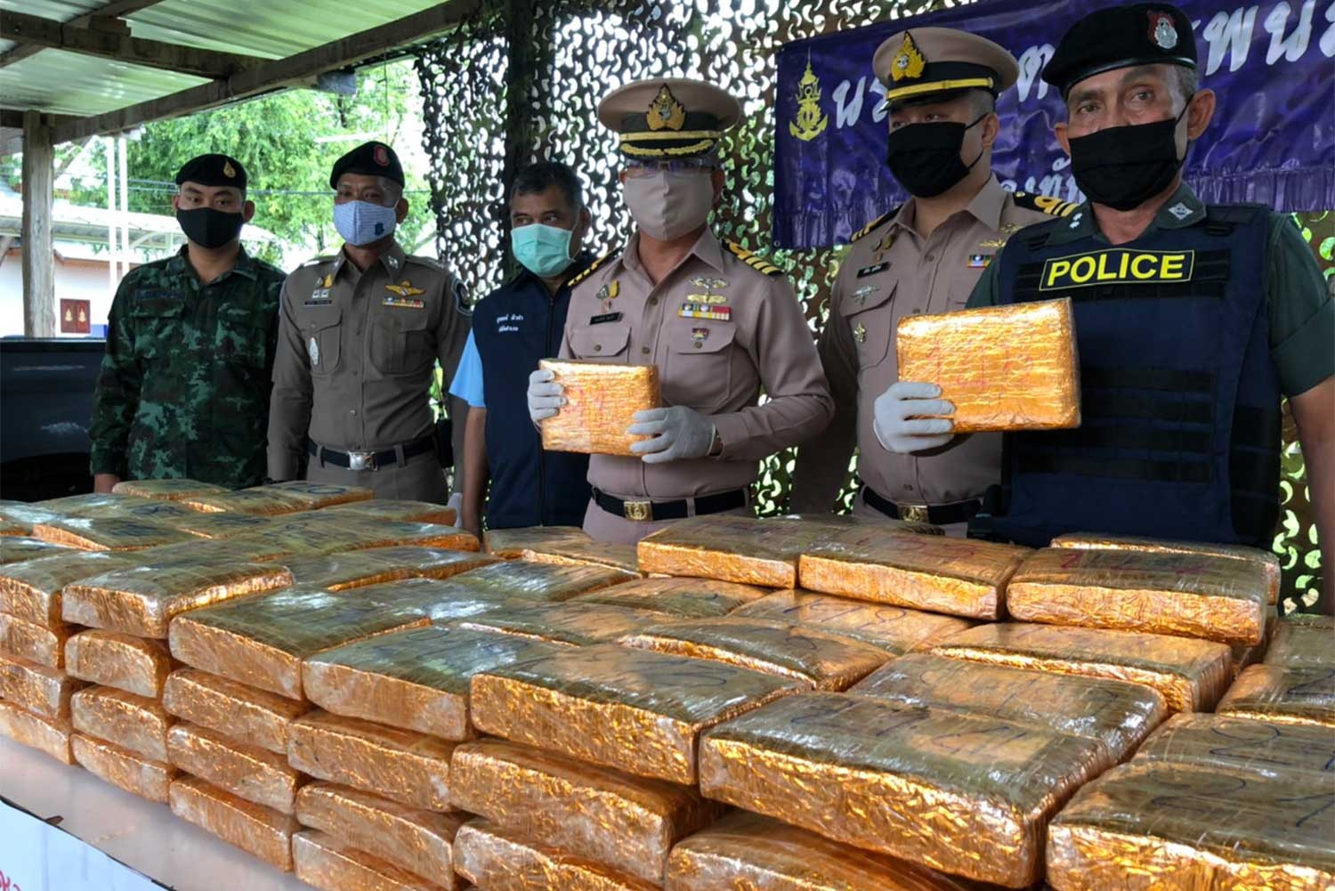 Navy officers display compressed marijuana seized in That Phanom district of Nakhon Phanom. (Photo: Pattanapong Sripiachai)