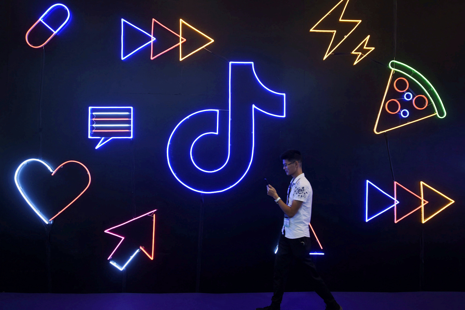A man walks past a display featuring the TikTok logo at an IT fair in Hangzhou, China in November. (Reuters File Photo)
