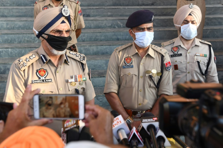 Punjab Police speak to media in Tarn Taran district on Saturday after dozens of people died from poisoned alcohol.