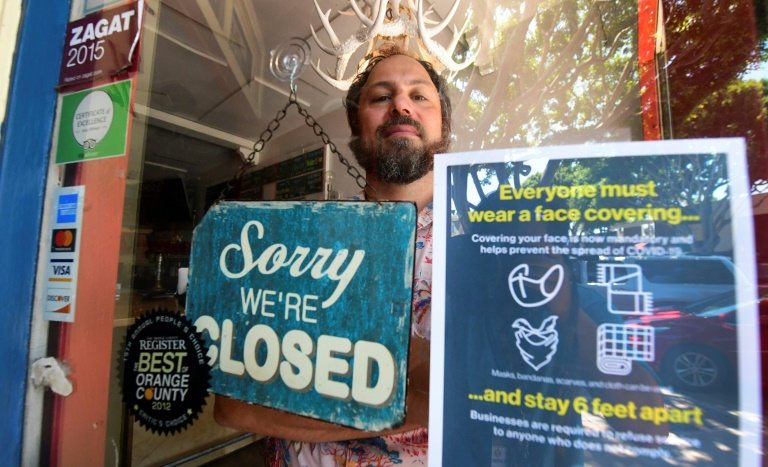 Gabriel Gordon stands behind the glass entrance door to his restaurant Beachwood BBQ, in Seal Beach, Californian, which he has been forced to permanently shut down because of the coronavirus pandemic.