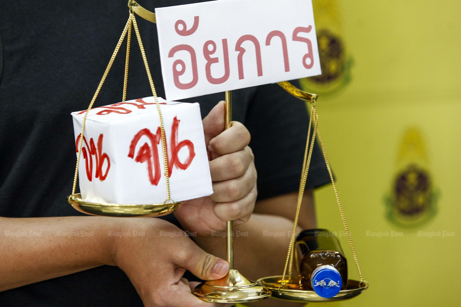 A representative of law students nationwide holds a tilted 'prosecution' scale, with a Red Bull energy drink bottle on one side and a cube with the word 'poor' on all sides on the other. The group asked the National Anti-Corruption Commission (NACC) to set up a panel to investigate public prosecutors after they decided to drop all charges against Red Bull scion Vorayutn Yoovidhya at the NACC office in Bangkok on Thursday. (Photo by Pattarapong Chatpattarasill)