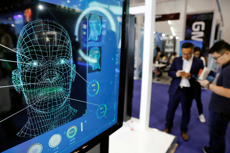 FILE PHOTO: Visitors check their phones behind the screen advertising facial recognition software during Global Mobile Internet Conference (GMIC) at the National Convention in Beijing, China April 27, 2018. (Reuters)