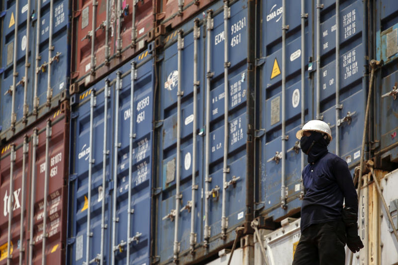 A worker stands next to shipping containers on a ship at a port in Bangkok, Thailand, March 25, 2016. (Reuters file photo)