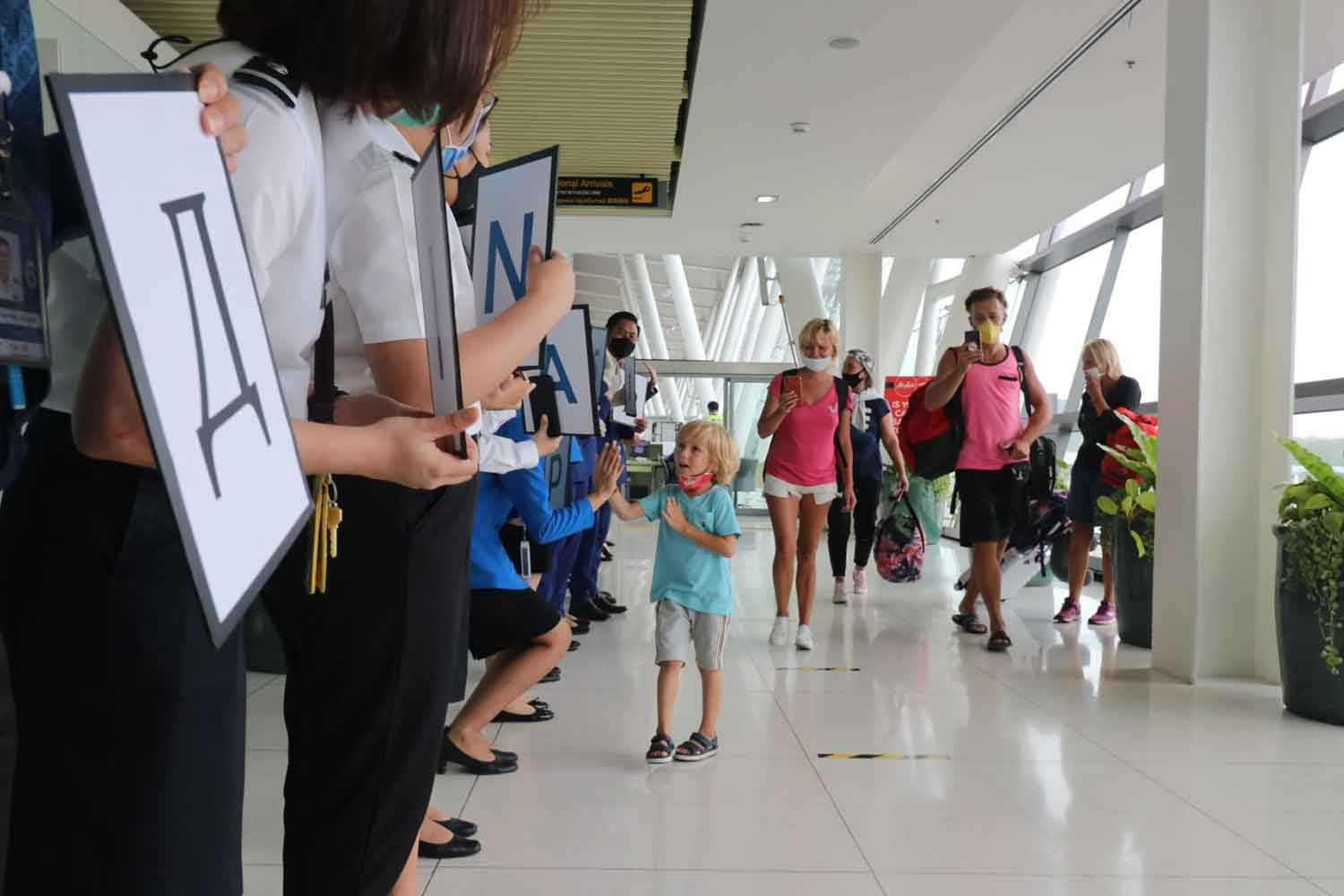 Phuket airport staff stand in line to bid farewell to stranded Russian tourists who flew home on a special flight on Tuesday. (Photo: Achadtaya Chuenniran)