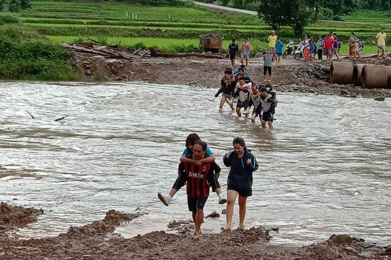 A man carries a child across the Mae Lao River to go to school as other flood victims follow.(Photo by Saiarun Pinaduang)
