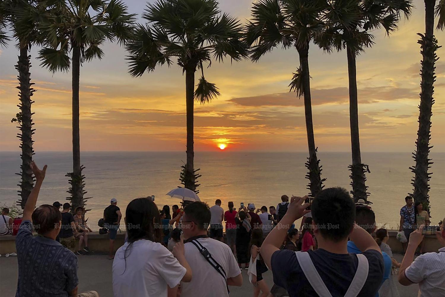 Tourists take sunset pictures at Promthep Cape in Phuket. A new plan aims to draw at least 500,000 tourists to Thailand. (Photo by Sarot Meksophawannakul)