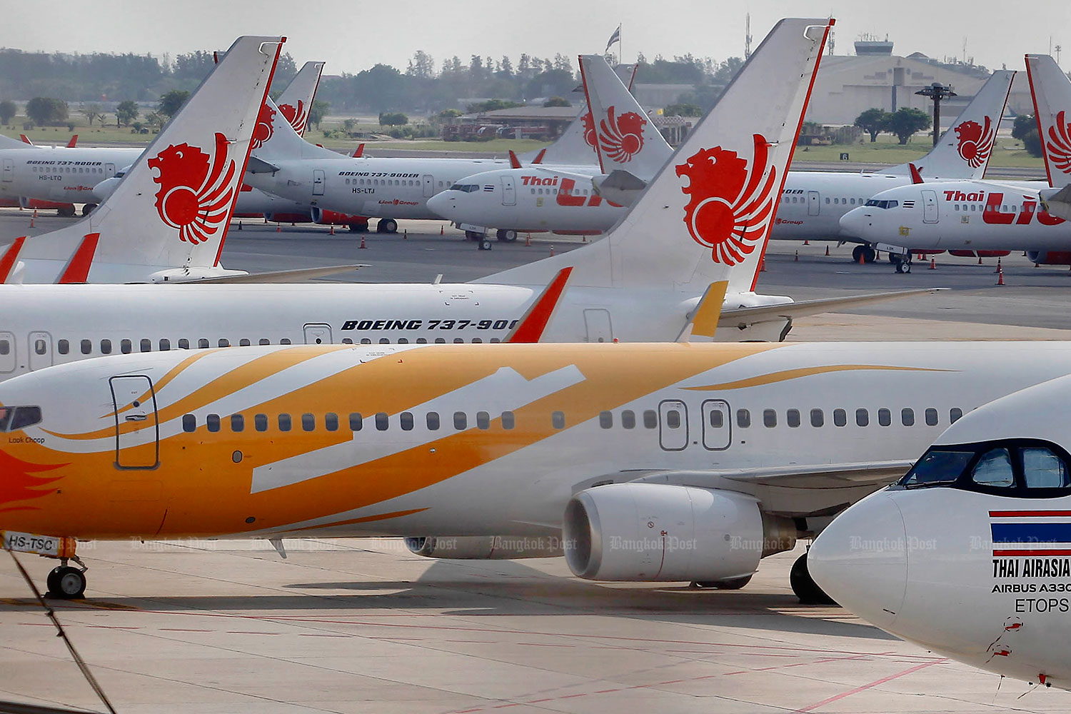 Thai Lion Air, Nok Air and AirAsia aircraft sit on the tarmac at Don Mueang airport. Soft loans for the airlines have been delayed.(Photo by Pattarapong Chatpattarasill)