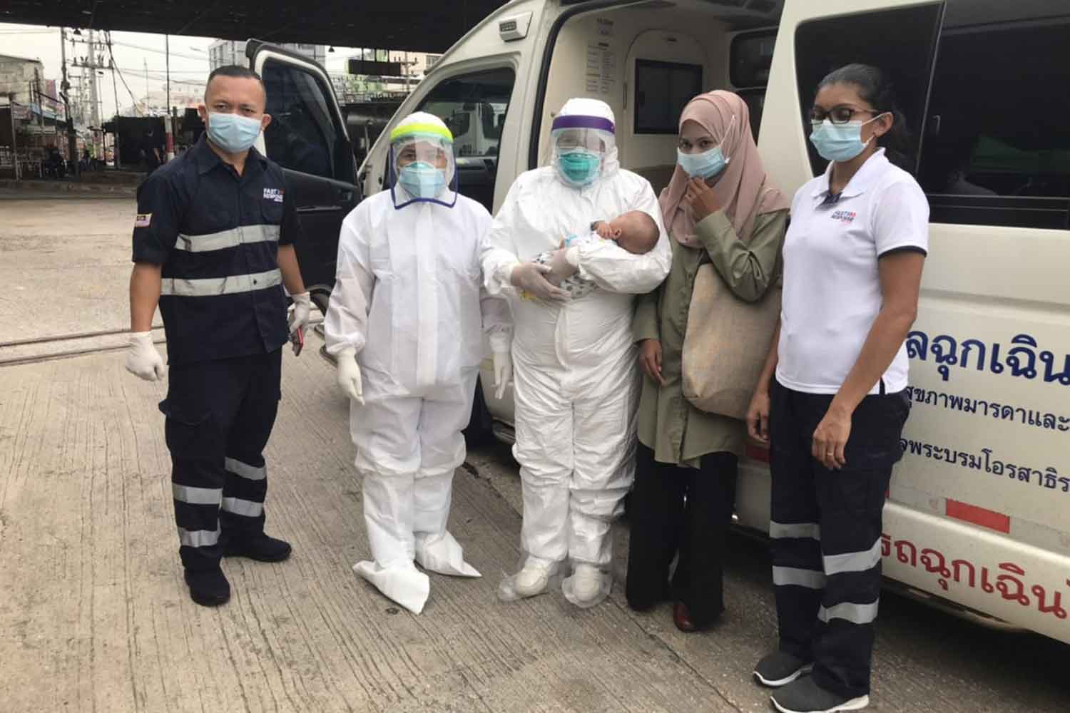 Nurahaleesa Jeh-awae, 18, second right, with health officials, one holding her baby, at the Sadao border crossing in Songkhla province on Thursday morning. (Photo: Abdullah Benjakat)
