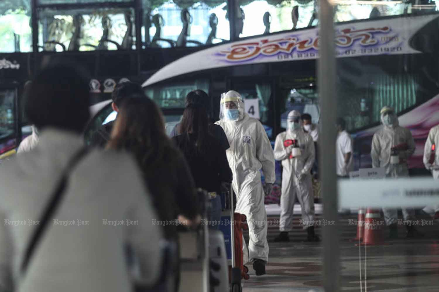 Returnees walk to their bus, heading for quarantine, at Suvarnabhumi airport in Samut Prakan province. The government reported 15 new Covid-19 cases on Friday. (Photo: Arnun Chonmahatrakool)