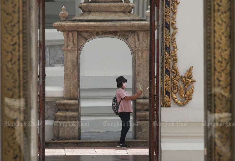 A tourist takes a photo at Wat Pho on June 24. Thailand could receive as few as 6.14 million foreign tourists next year in a worst-case scenario, officials now say. (Photo by Arnun Chonmahatrakool)