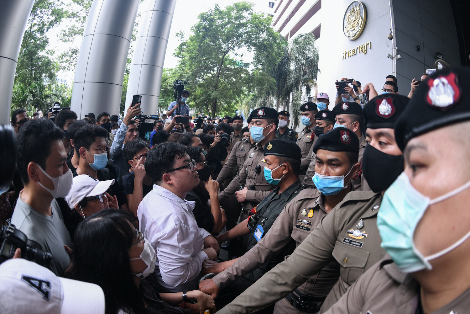 """Pro-democracy protesters stand outside the Criminal Court building demanding that a representative be allowed inside where Anon Nampa and Panupong """"Mike Rayong"""" Jaadnok were facing a detention hearing on Saturday. (Reuters Photo)"""