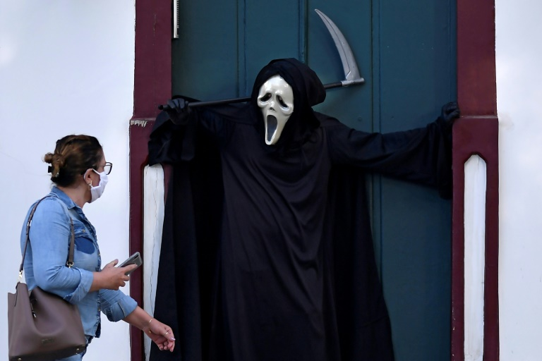 A woman looks at Brazilian actor Fabio de Almeida disguised as death to raise awareness of the importance of wearing face masks and social distancing, in Formiga, Minas Gerais.