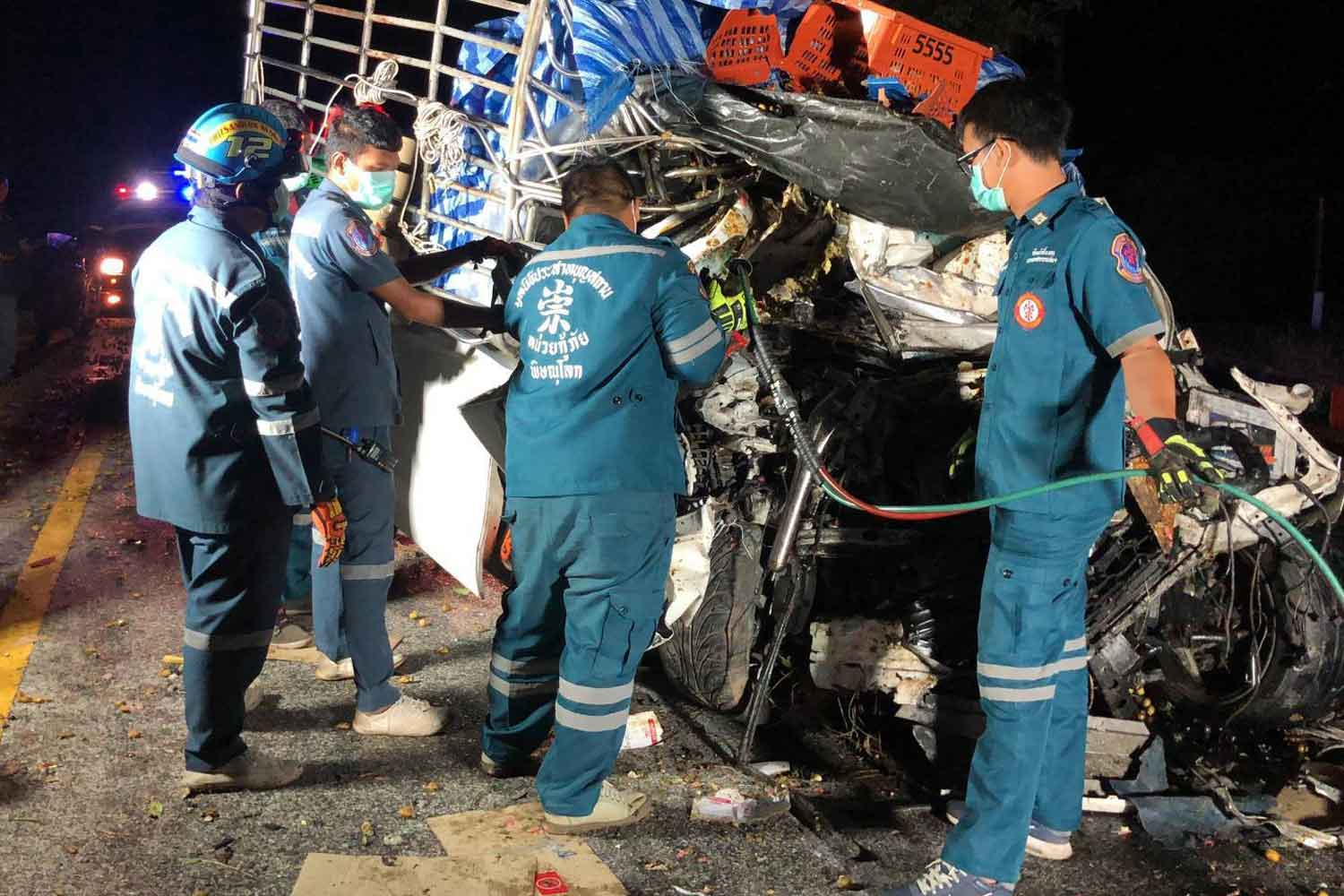 Rescuers examine one of the two pickup trucks that collided head-on on Highway 11 in Phitsanulok on Monday morning. Both drivers were trapped in their vehicles. One was killed and the other severely injured. (Photo: Chinnawat Singha)