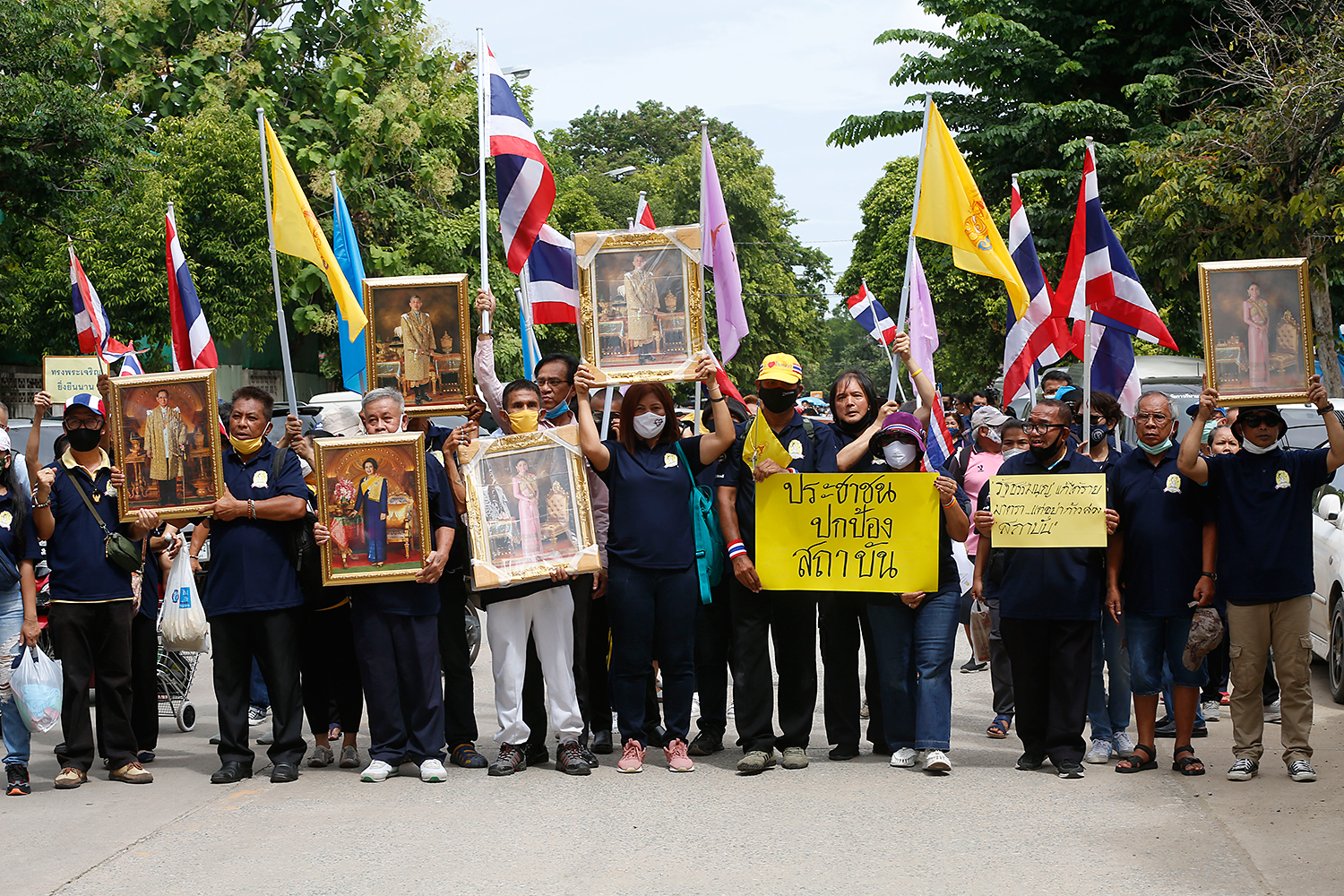For king and country: A group of royalist supporters hold framed pictures of members of the royal family as they rally outside parliament and call on the government to protect the institution on Monday. (Photo by Pornprom Satrabhaya)