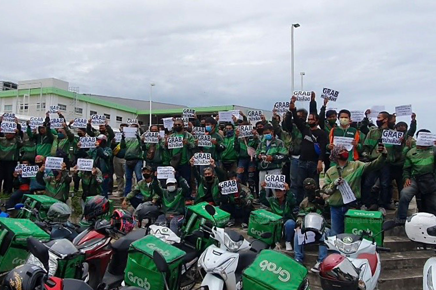 Around 100 GrabFood riders went on strike and rallied behind the Big C department store in Pattaya last week.(Photo by Chaiyot Pupattanapong)
