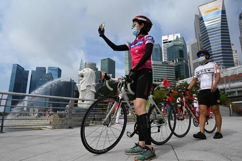 A cyclist takes a photo next to the Merlion statue in Singapore on Sunday. (AFP photo)