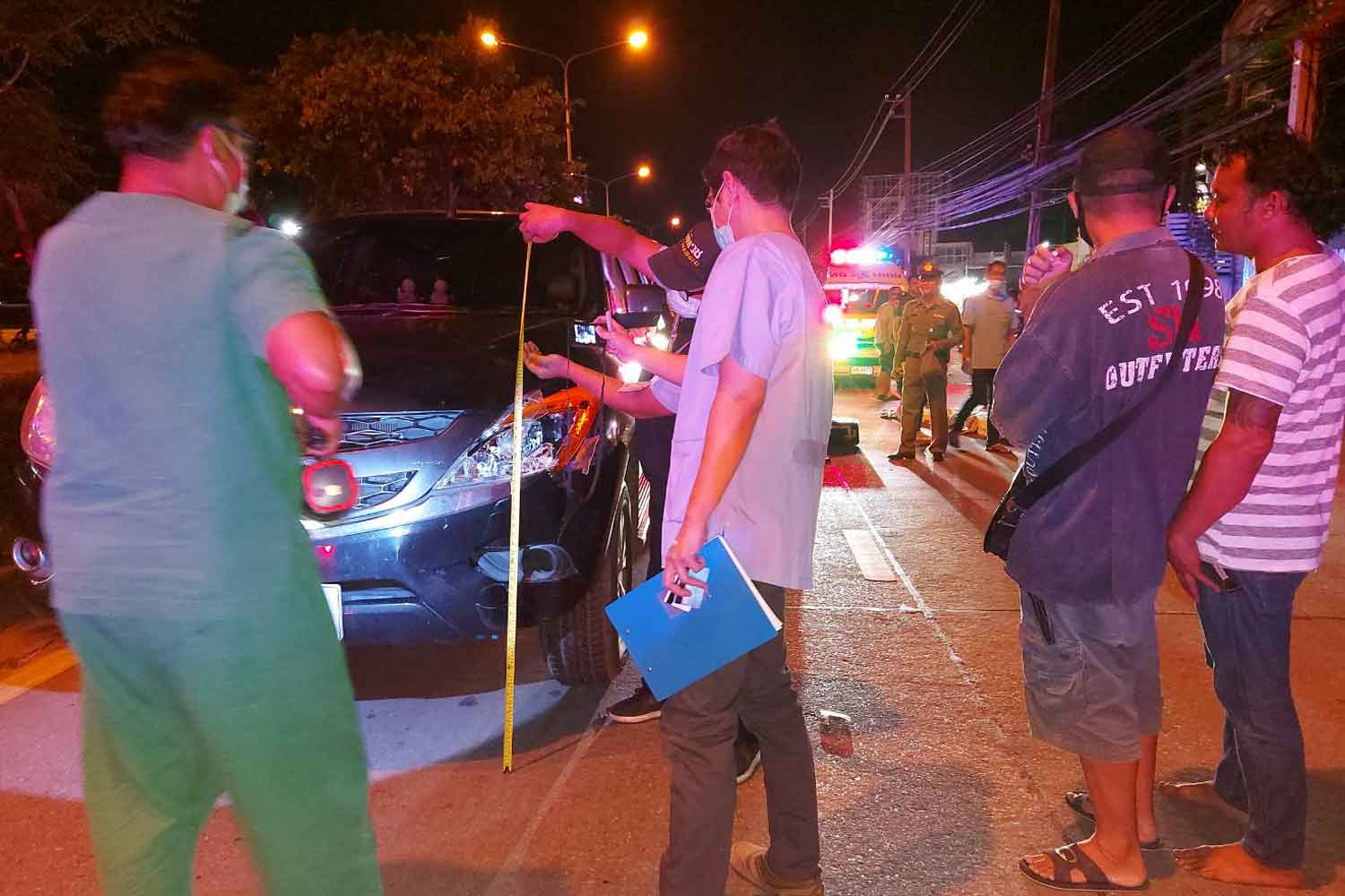 A police officer takes measurements at the scene where a pickup struck and killed an elderly woman crossing a busy road in Muang district, Nakhon Ratchasima, on Monday night. (Photo: Prasit Tangprasert)