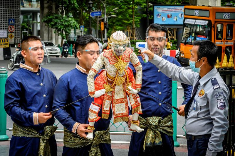 FILE PHOTO: A security guard pretends to take the temperature of a traditional Thai Hanuman puppet with a face shield held by its puppeteers at the Erawan Shrine in Bangkok on July 13, 2020. (AFP)