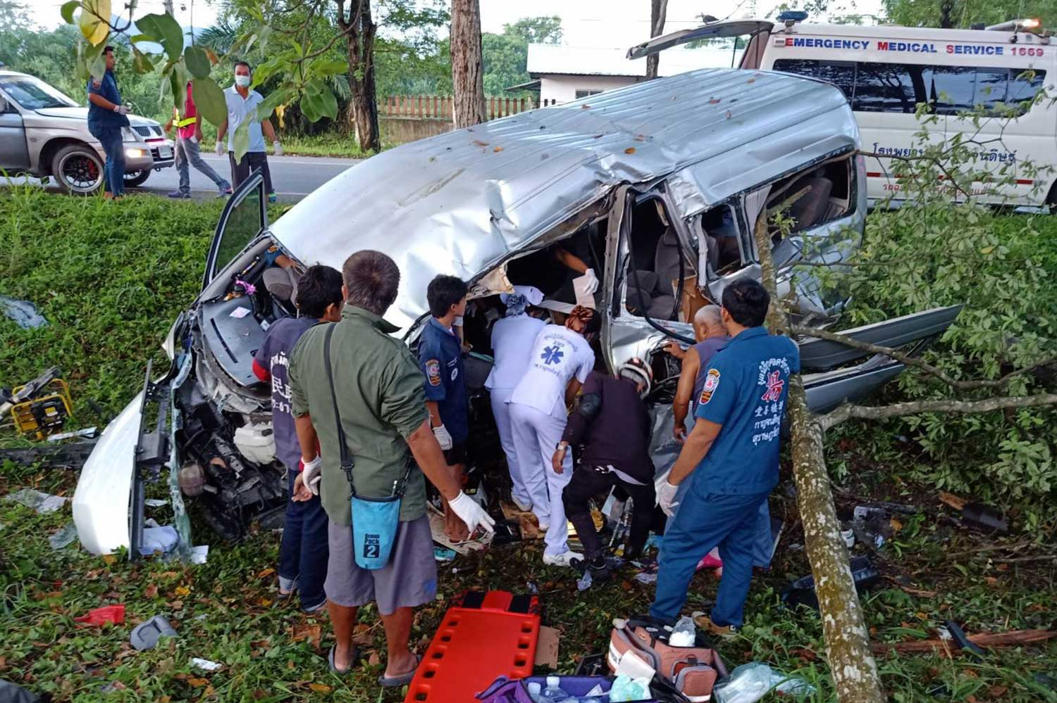 Rescue workers try to retrieve injured people from the wreckage of a van after it plunged into a ditch dividing the road in Kanchanadit district, Surat Thani on Tuesday morning. One woman was killed and 10 others injured. (Photo by Kusolsattha Surat Thani rescue foundation)