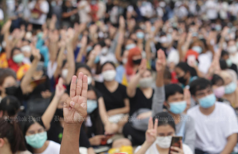 Young anti-government protesters flash the three-finger anti-coup sign during a rally at Thammasat University's Rangsit campus on Monday. (Photo by Apichit Jinakul)