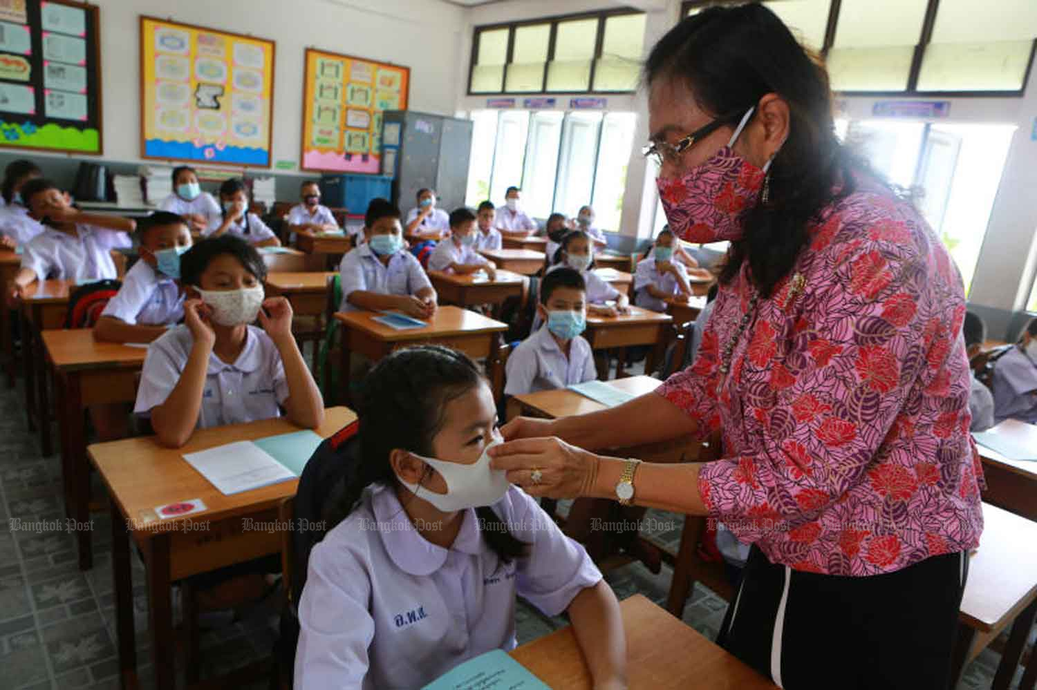 Students are advised on how to wear face masks properly when full-scale school teaching resumes at Intarumphun School in Samut Prakan province on Thursday. Meanwhile, the government reported three new Covid-19 cases among returnees from India and Singapore. (Photo by Somchai Poomlard)