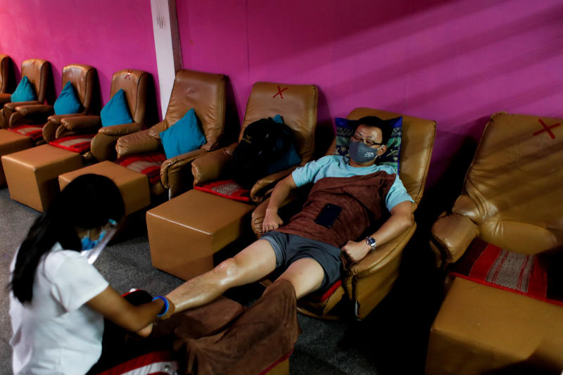 A therapist wearing a face shield works in a traditional massage shop in Bangkok on June 3, 2020. The shop reopened after the government eased isolation measures to prevent the coronavirus spread. (Reuters photo)
