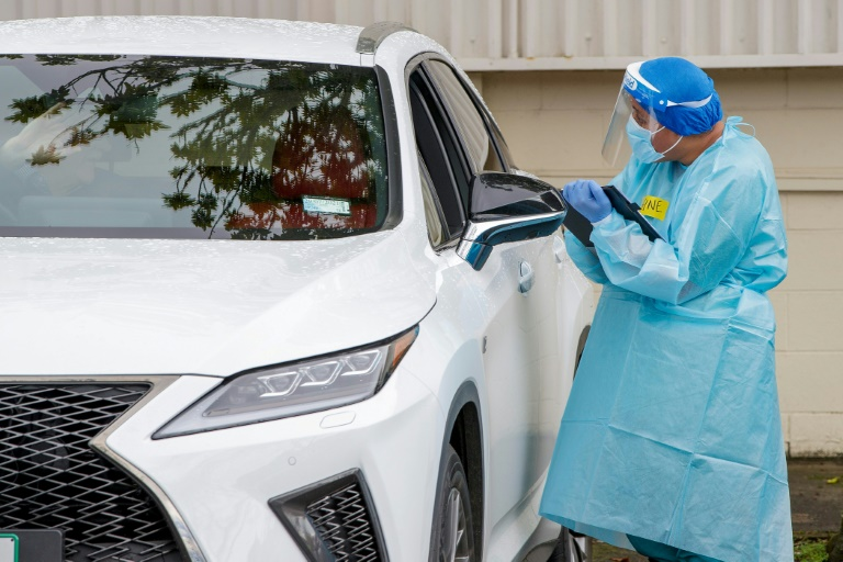 A health worker tests a car passenger at a Covid-19 testing centre in the suburb of Northcote in Auckland.