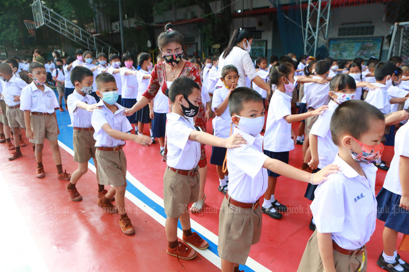 Pupils check their distance apart during morning assembly at Intarumphun Anusorn School in Samut Prakan province on Thursday. (Photo: Somchai Poomlard)