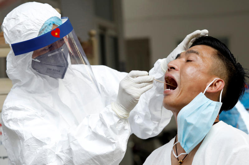 A medical specialist wearing a protective suit collects a swab sample from a traveller who has returned from Da Nang, at a testing centre for coronavirus disease in Hanoi on Monday. (Reuters photo)