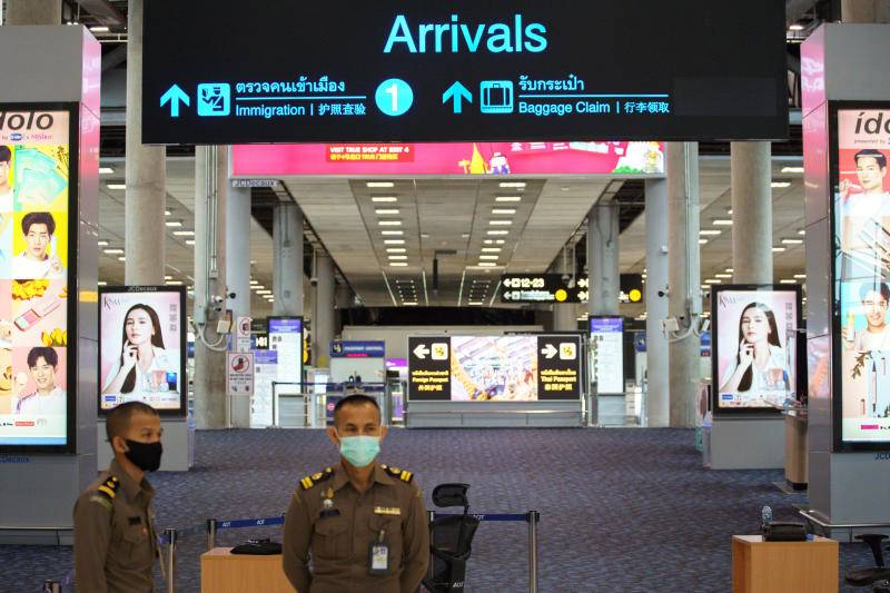 Immigration officers stand in front of an empty arrivals hall at Suvarnabhumi airport on June 3, 2020. (Reuters photo)