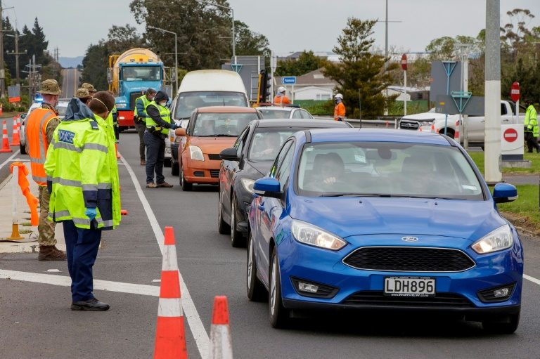 Police and military personnel check vehicles leaving Auckland as New Zealand rushes to track the source of a sudden return of the coronavirus.
