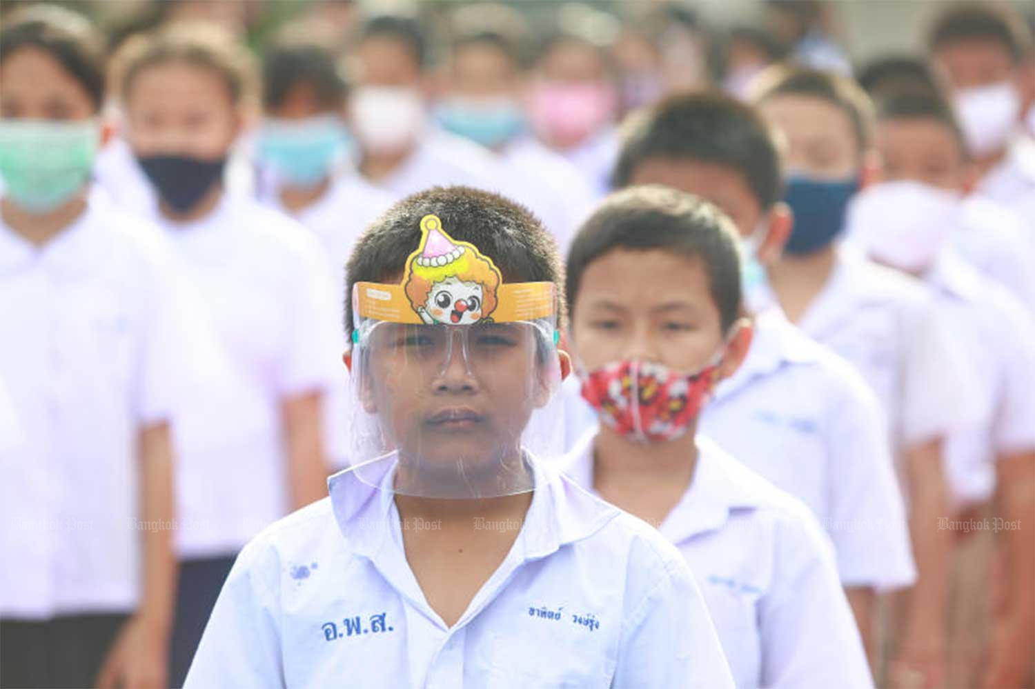 Pupils at Intarumphun Anusorn School in Samut Prakan province wear face shields and face masks to school on Thursday. (Photo by Somchai Poomlard)