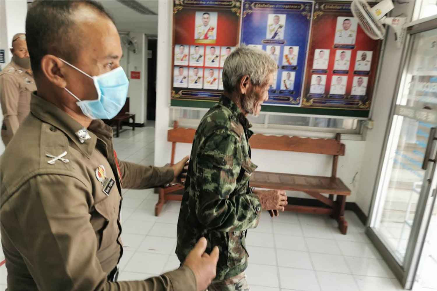Ka-ed Miadtiab, 74, right, is escorted by police at Prakhon Chai police station in Buri Ram. He was charged with murder for stabbing to death his nephew after a row on Sunday. (Photo by Surachai Piragsa)