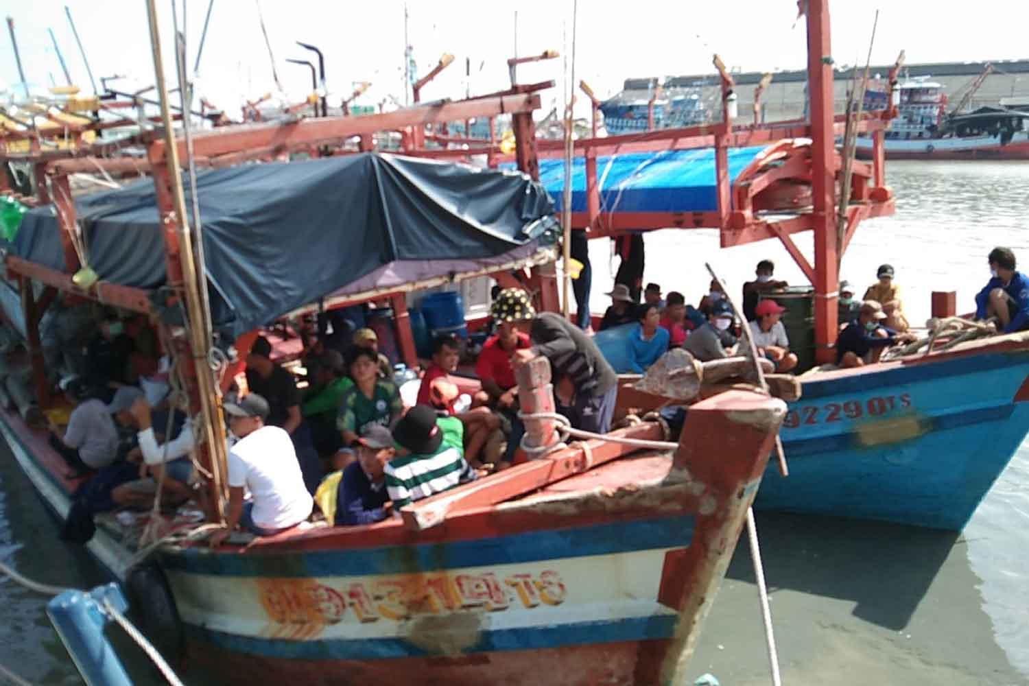 Two of the four seized Vietnamese fishing boats, and their crews, found trawling illegally in Thai waters, moored at Pattani boat landing. (Photo: Abdullah Benjakat)